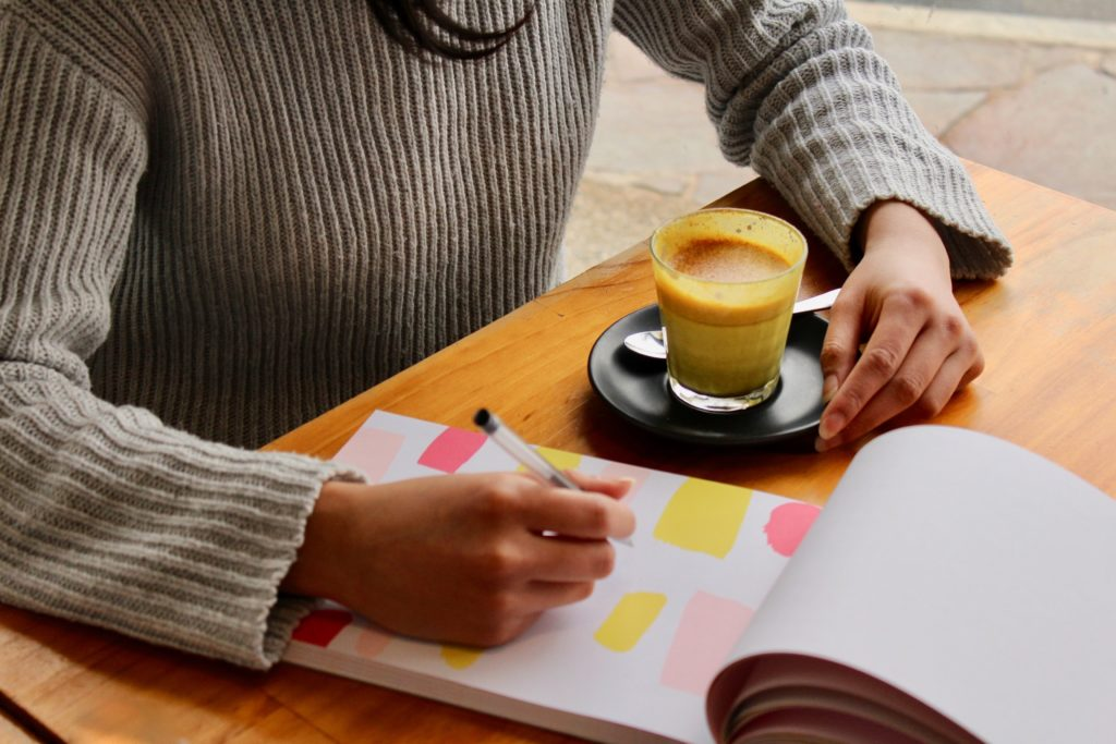 Person at a table with a notepad and coffee